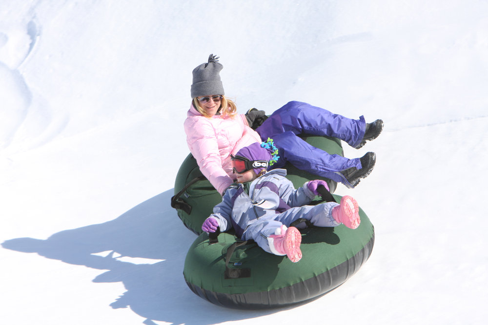 A mother and child go tubing at Boyne Mountain Resort, Michigan