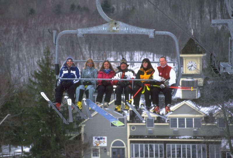 A chairlift with skiers and snowboarders in Jiminy Peak, Massacheusetts