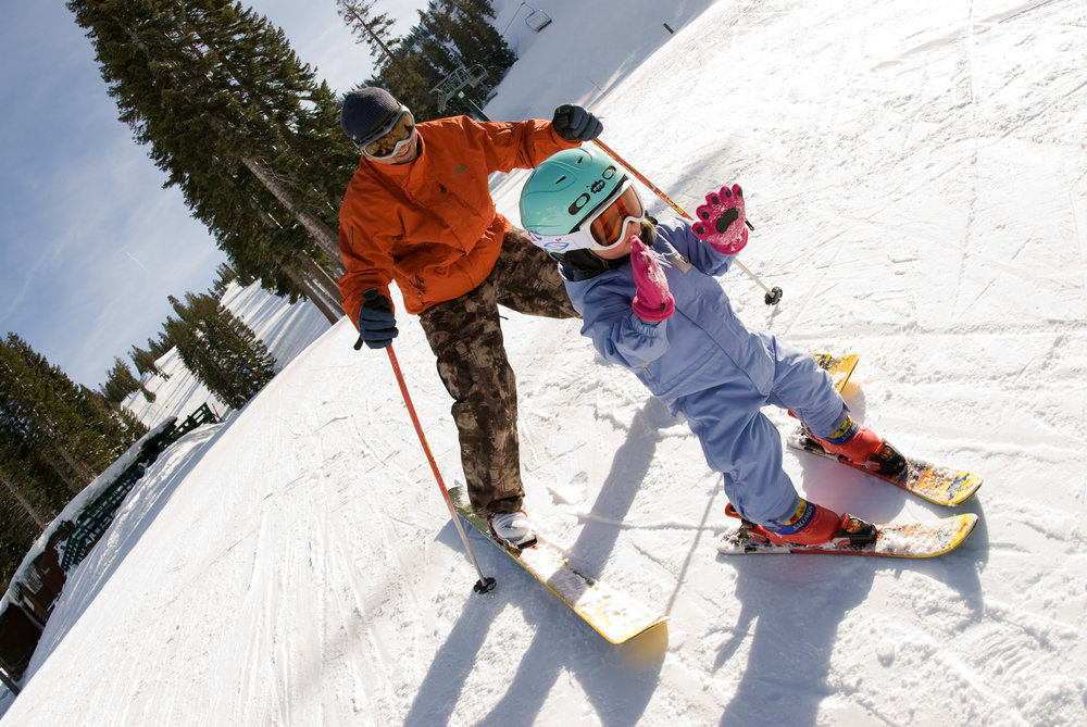 A father and daughter make their way down the mountain in Alpine Meadows, California