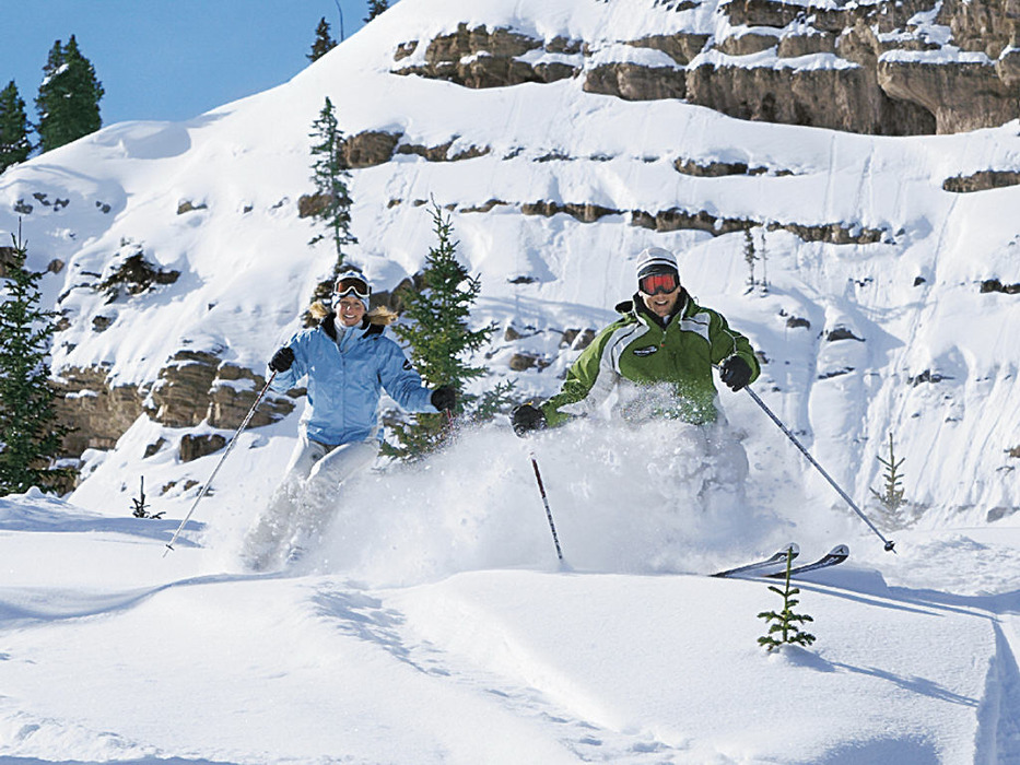 Two skiers in powder at Aspen Highlands, Colorado