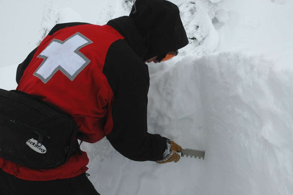 A ski patroller tests snow stability in a snow pit.