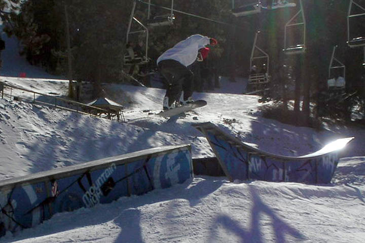 A snowboarder gets air off a rail in Mountain High, California