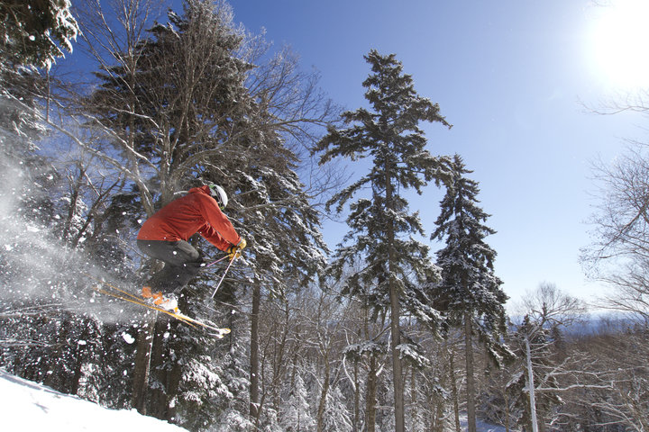 A skier takes flight in the glades at Okemo.