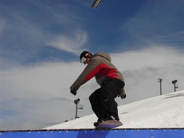 A snowboarder performs a trick in Snow Valley, California