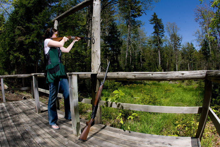 Girl shooting clays in woods of Snowshoe in summer