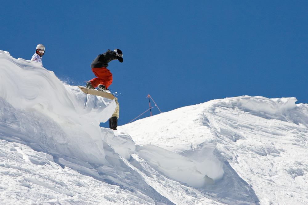 A snowboarder descending Aspen Snowmass.