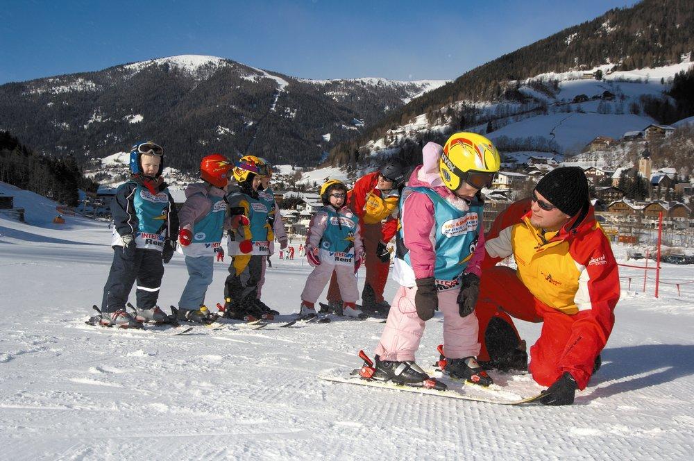Instructor teaching little student how to snowplow in Bad Kleinkirchheim
