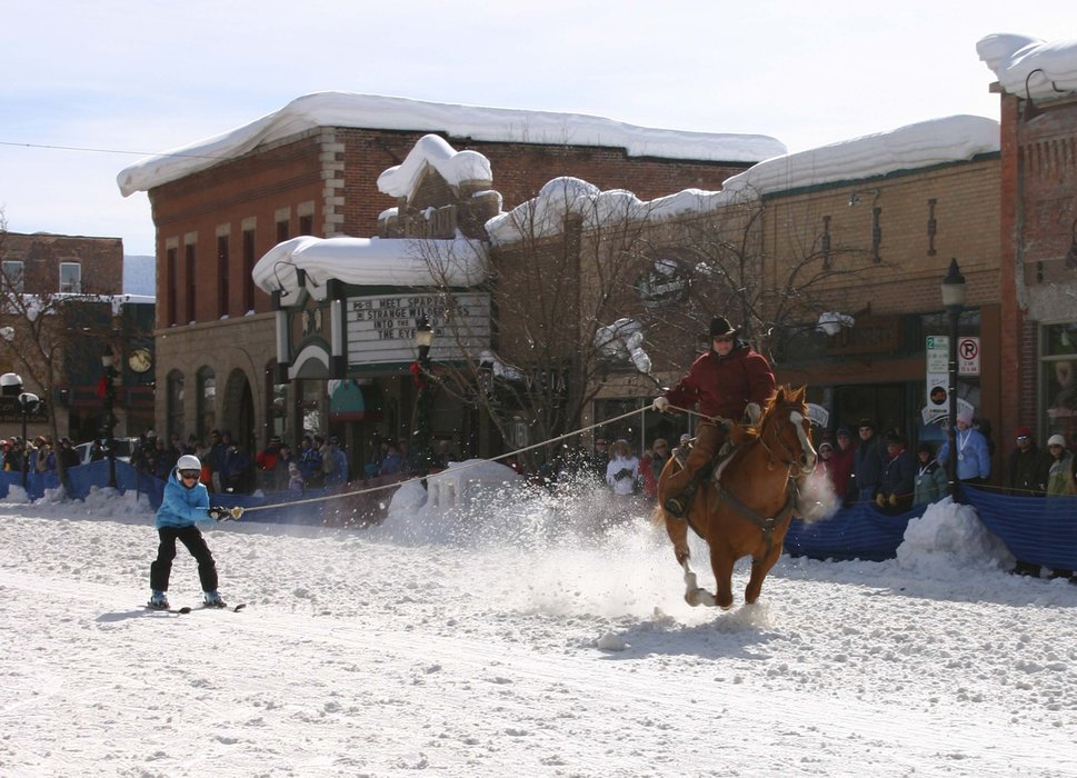 Skier getting a ride from a cowboy at Steamboat's Winter Carnival.