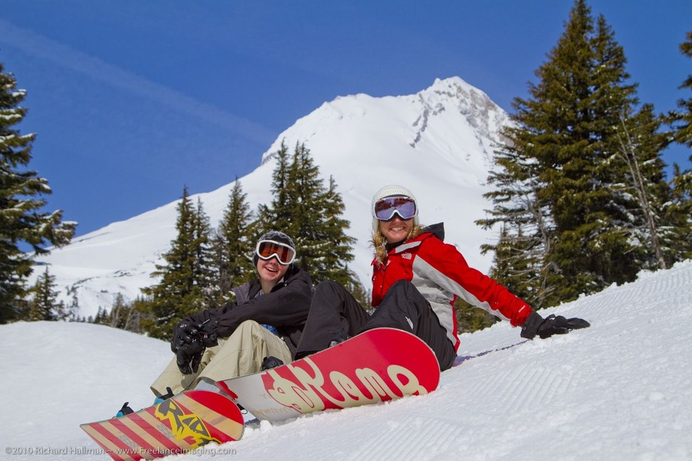 A pair of snowboarders taking a break on the slopes of Mount Hood Meadows, Oregon. Image by Richard Hallman.