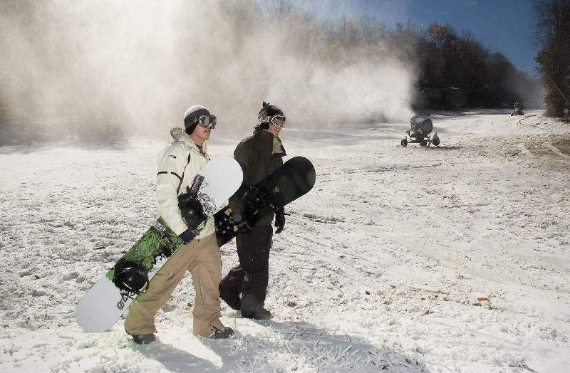 Two snowboarders head to the chairlifts at Sugar Mountain Resort, North Carolina