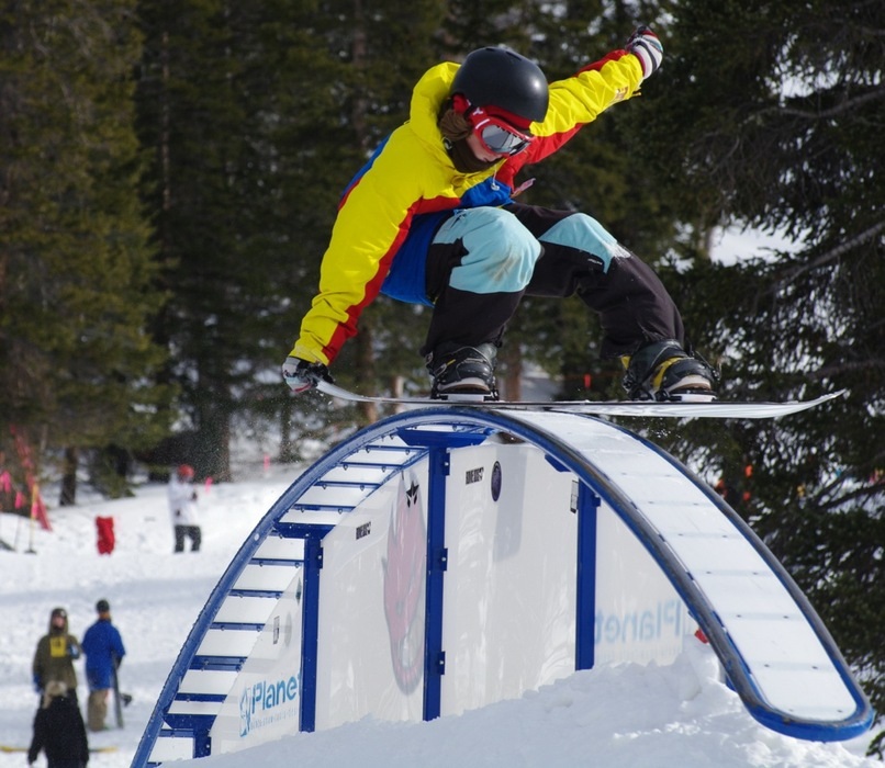 Snowboarder hitting the terrain park.
