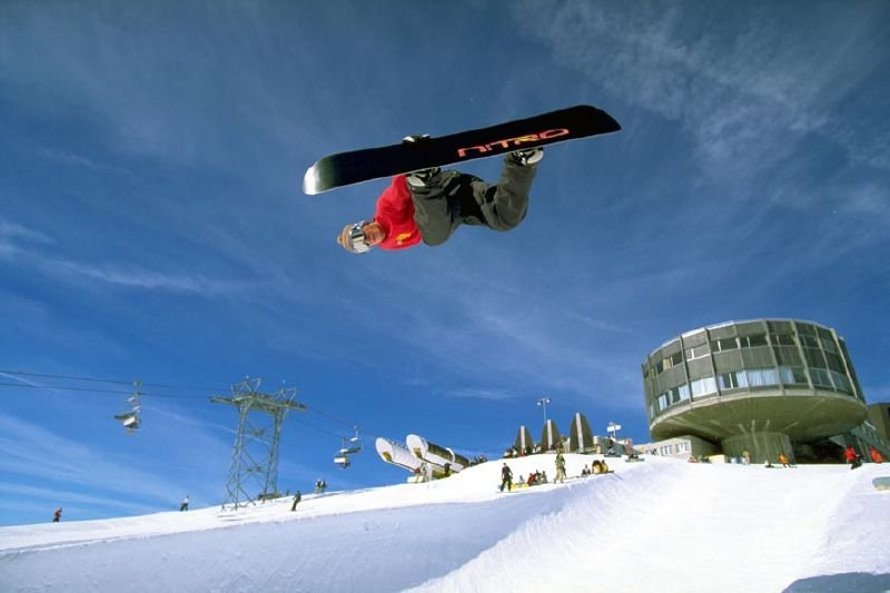 A snowboarder catching air at the Laax superpipe.
