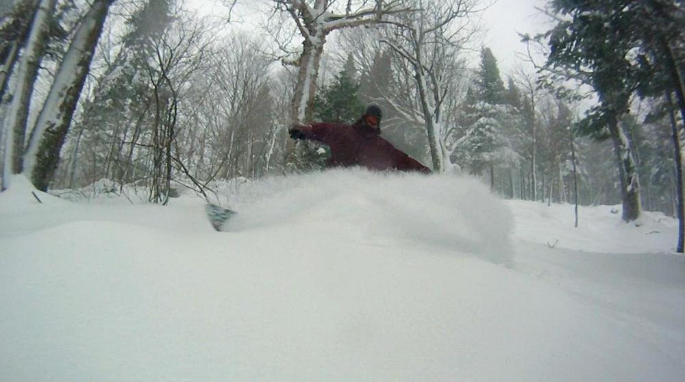A snowboarder finds a fresh powder stash at Mont Sainte-Anne. Photo Courtesy of Mont Sainte-Anne.
