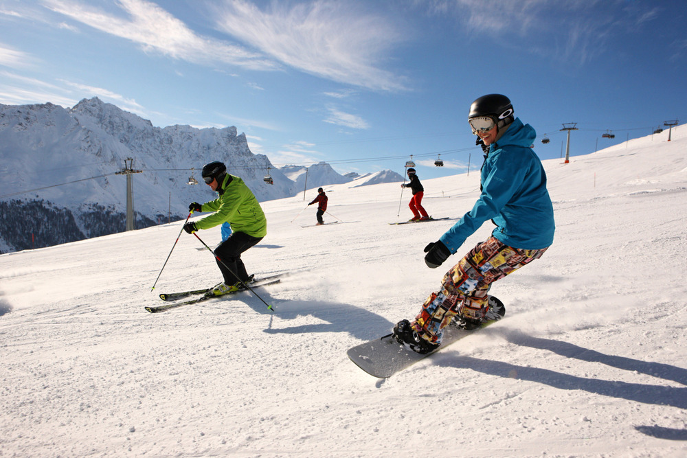 Skiers and snowboarders on the slope in Savognin