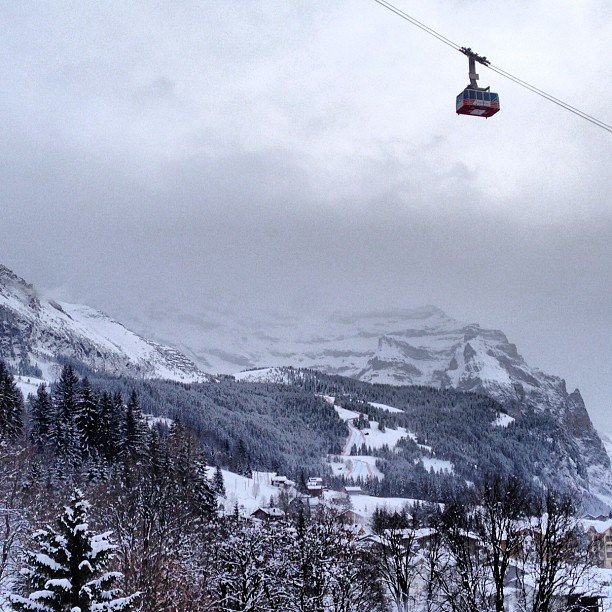 A tram car rises out of the town of Wengen with the Downhill track in the distance.