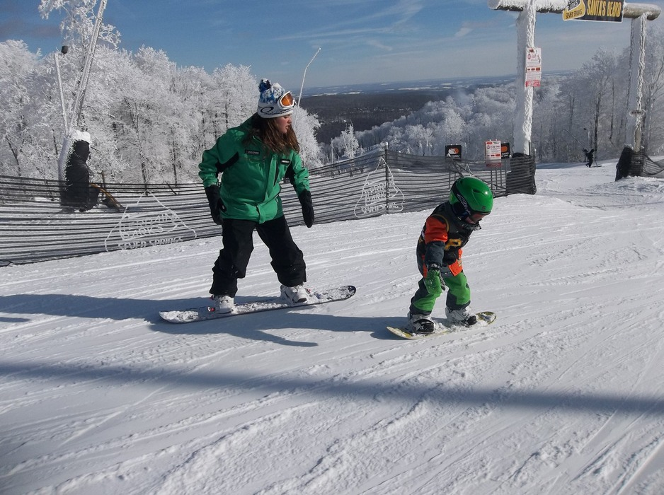 A young snowboarder riding with his snowboard instructor. Photo Courtesy of Seven Springs.