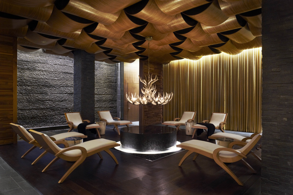 The breathtaking relaxation lounge is outfitted with teak chaise lounges, a marble infinity pool and a floor-to-ceiling water feature that cascades down rough-hewn granite to mimic the sound of a babbling brook. 