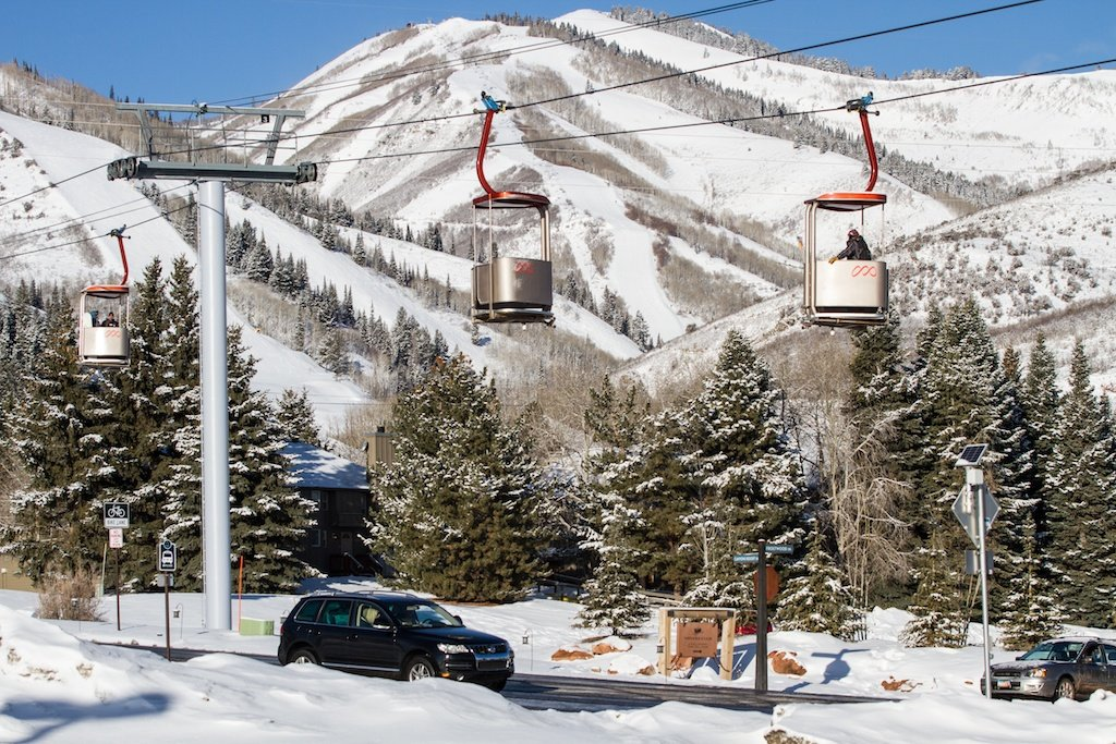 An open air gondola transports skiers to the mountain's base.