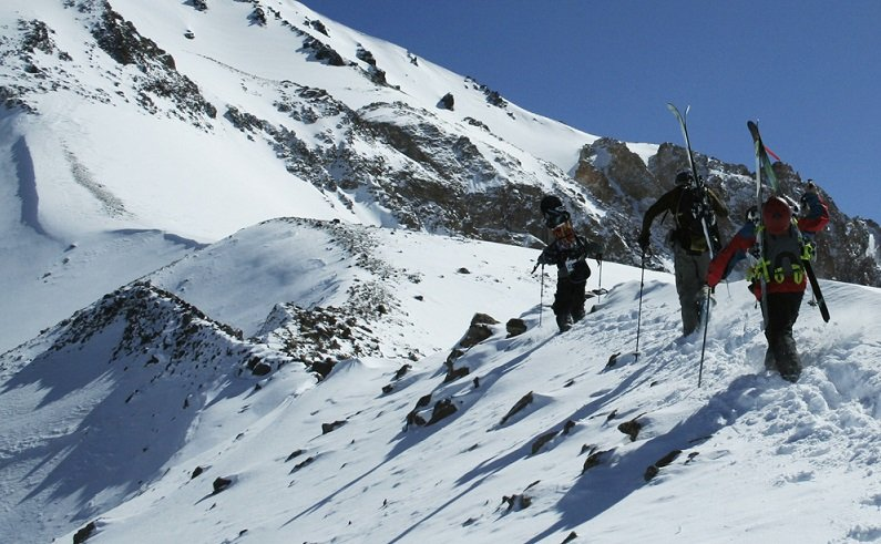 Three skiers hike for their turns in Portillo, Chile.