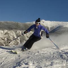 Cruising through soft snow with stoic view of the White Mountains. Photo Courtesy of Cannon Mountain.
