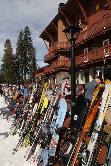 Stacks of skis and snowboards outside mountain hut