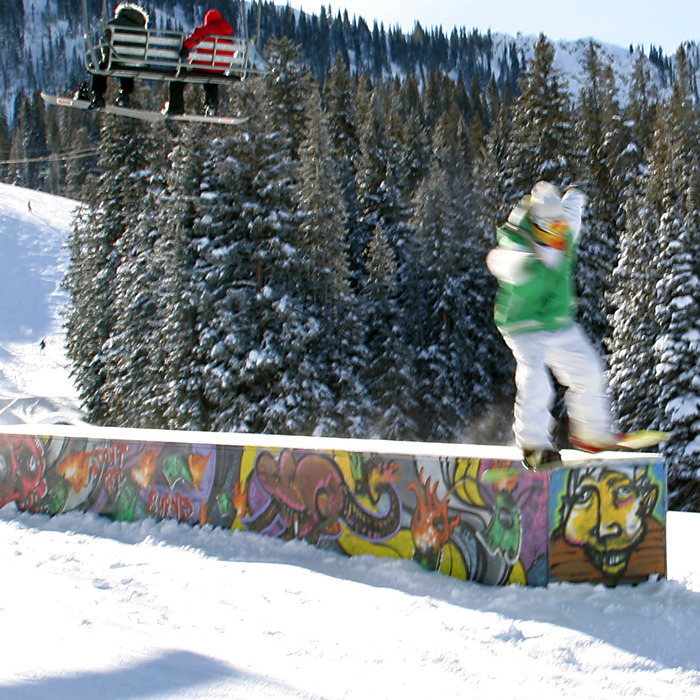 Snowboarder practising tricks on a box with chairlift overhead