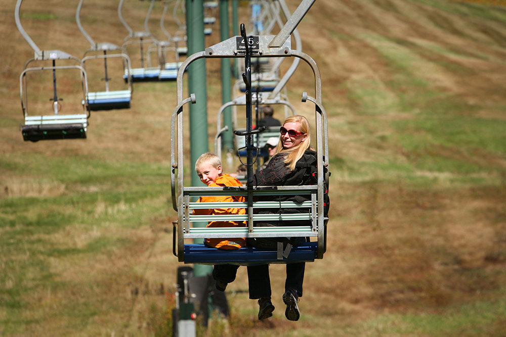 A mother and son riding a chairlift at Stowe Mountain Resort, Vermont