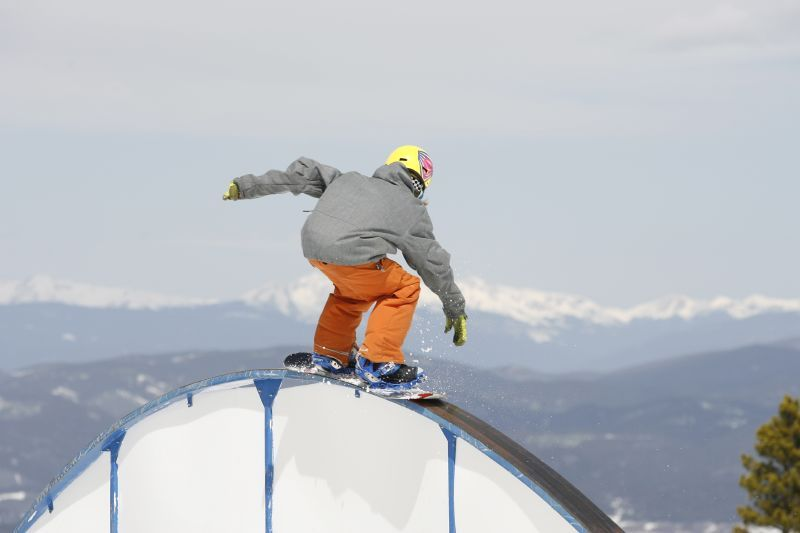 A snowboarder catches a ride on a rail in Winter Park Resort, Colorado