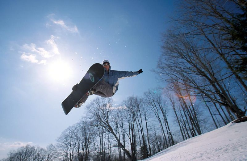A snowboarder in the air over Suicide Six, VT