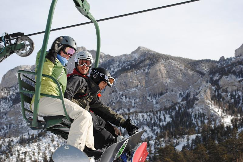 Trio of snowboarders on the lift at Las Vegas Ski & Snowboard Resort.