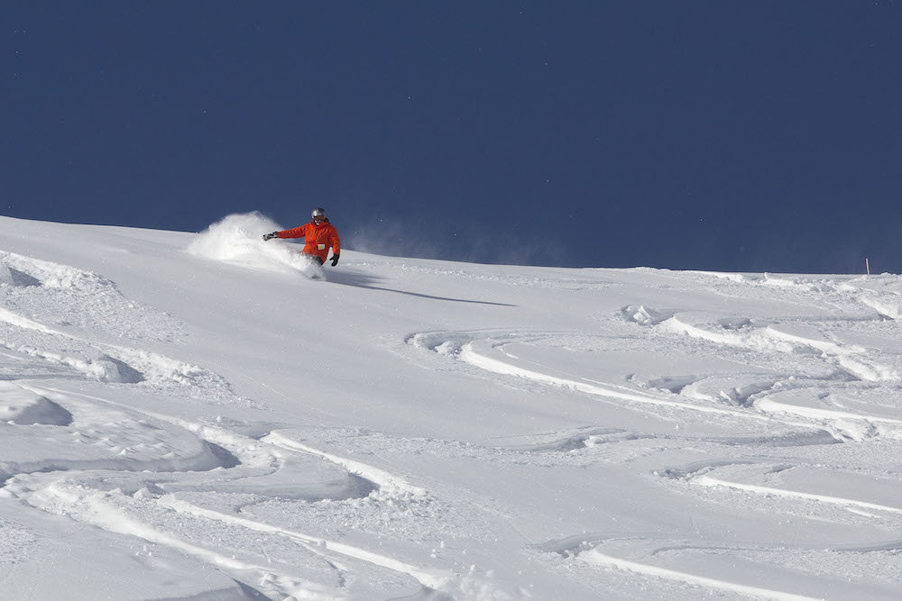 A snowboarder practices his powder 3's at Lake Louise. - © Lake Louise