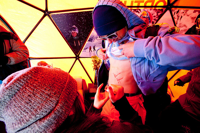 Devin Logan signs a fan's stomach in the North Face tent. - ©Sasha Coben
