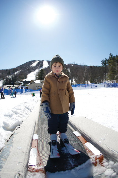 A boy skier rides the carpet lift at Mount Sunapee