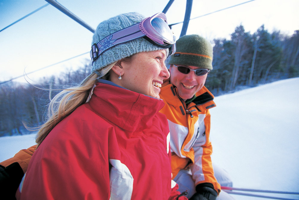 A young couple on a chairlift at Mount Sunapee.