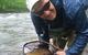 Fisherman showing his catch on Elk River, Snowshoe