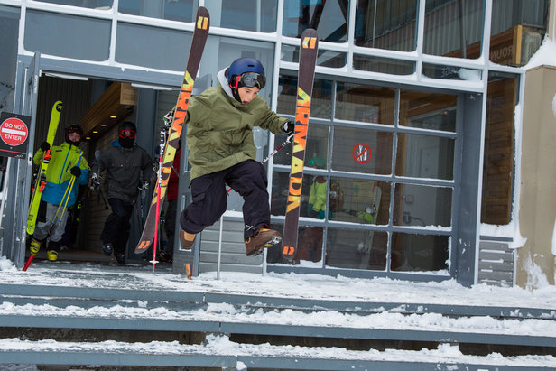 A young skier shoots out the gondola building doors in excitement for first run of the year at Whistler Blackcomb.